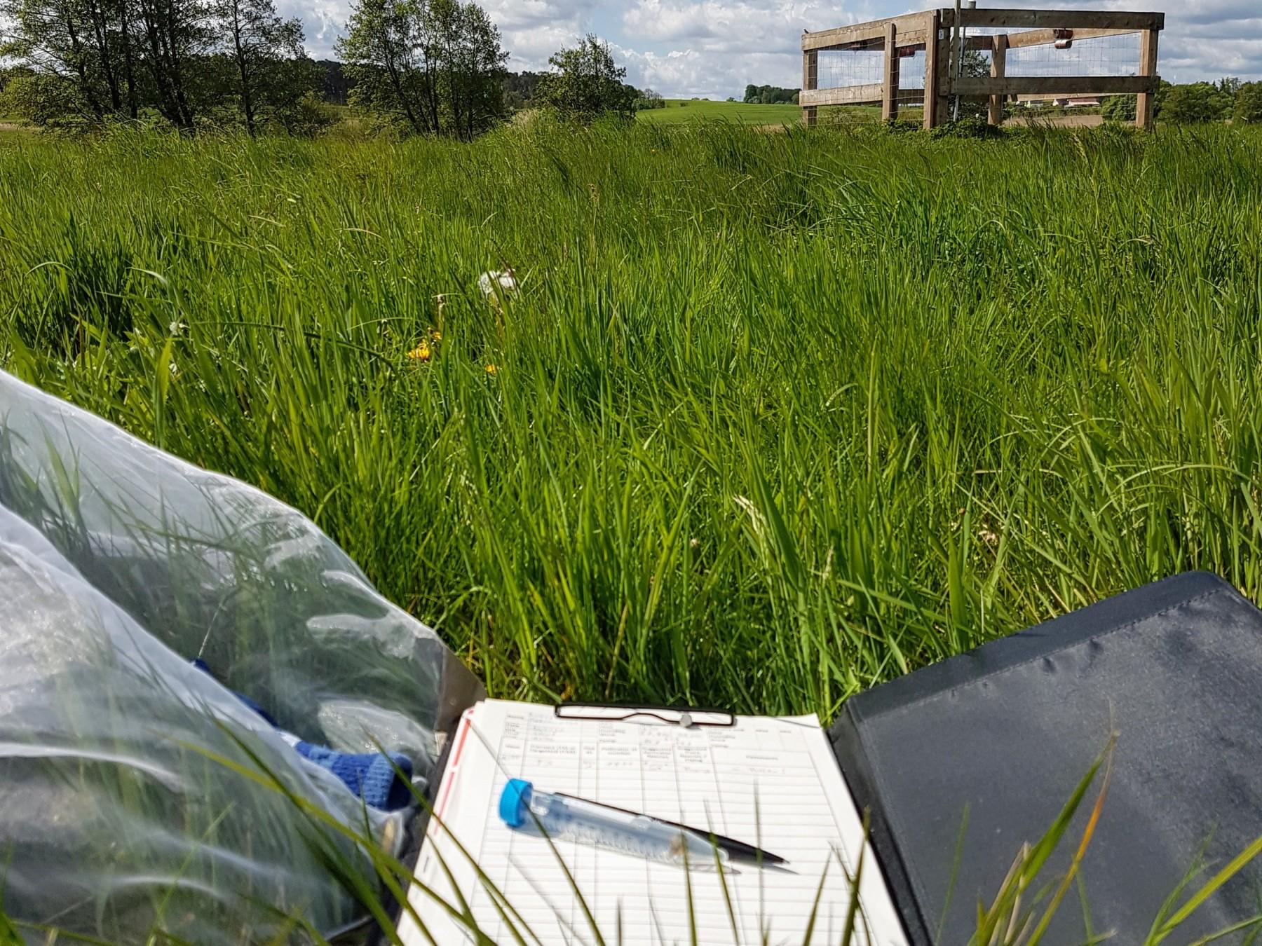 Wiese, im Hintergrund eine Klima-Station, im Vordergrund ein Klemmbrett mit Stift und Probenröhrchen